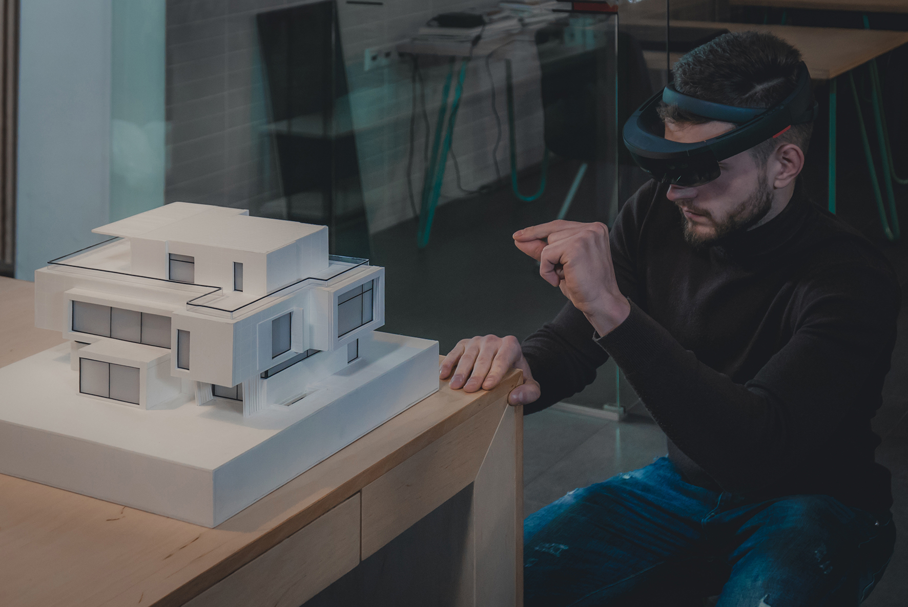 Young confident Caucasian male architect working on a private house project in the office using augmented reality glasses